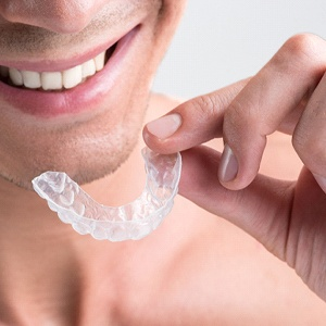 A man smiling while holding an Invisalign aligner