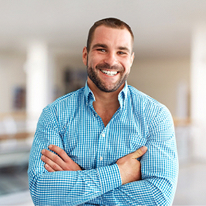 Smiling man with blue shirt crossing his arms