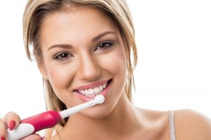 girl smiling with electric toothbrush