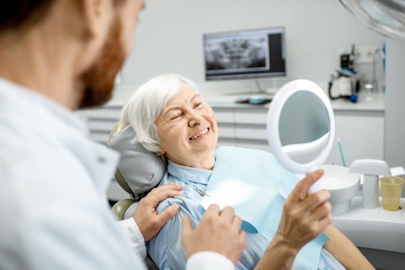 a dentist talking to an older lady who is looking at her new smile in the mirror