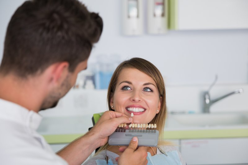a dentist using a shade guide to determine the color of a patient's teeth in Homer Glen