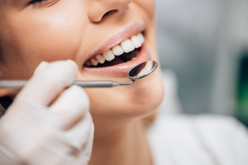 Cosmetic dentist examining a woman's smile